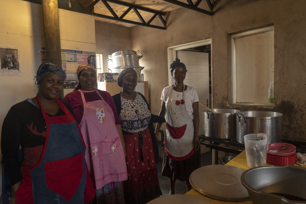 This image shows the four women who run the soup kitchen daily. They are standing in a row close to each other looking into the camera smiling. In front of them is the soup making apparatus. They are standing in the hemp building.